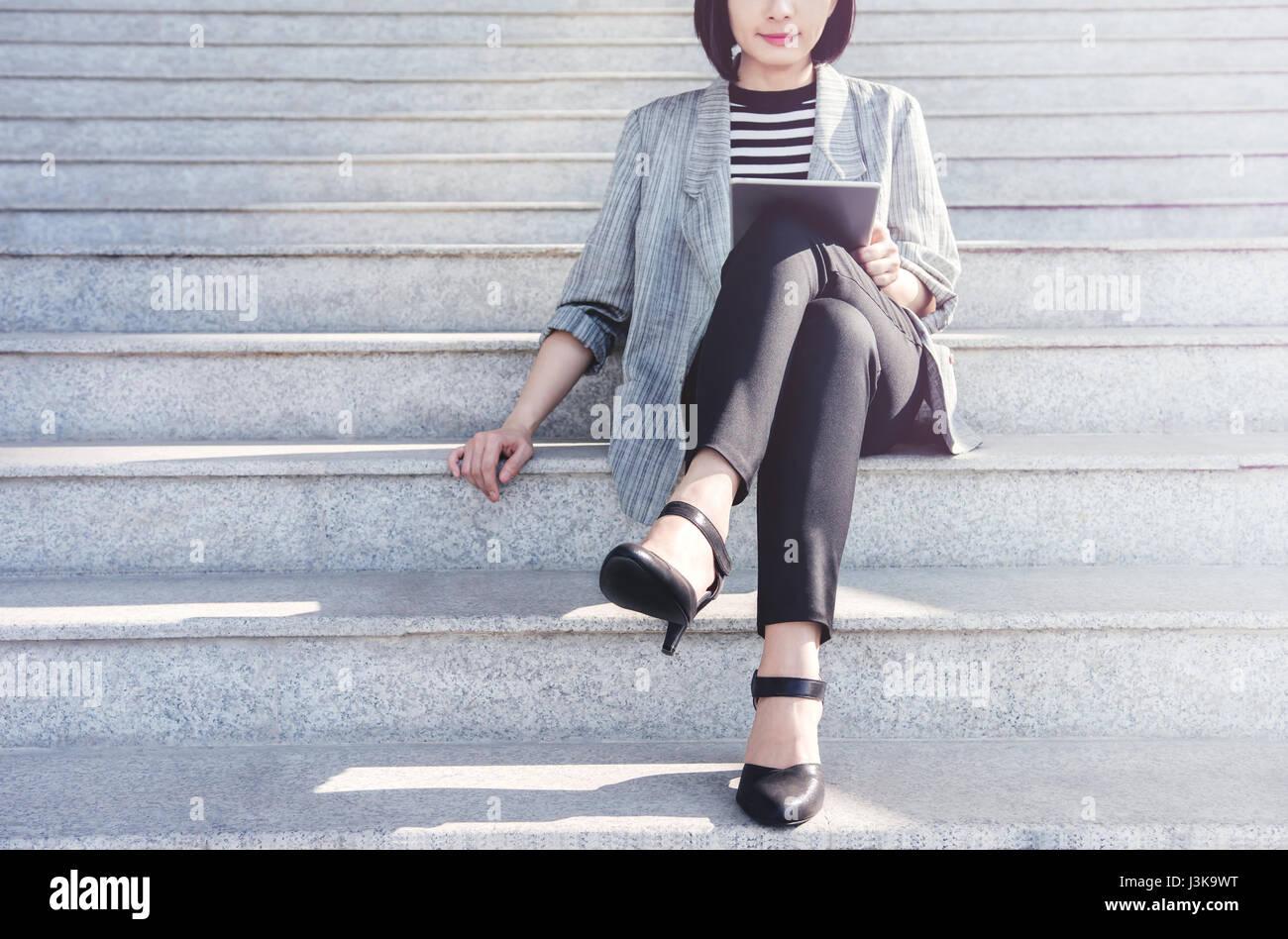 Negocio trabajar mujer sentarse y sonreír durante utilizando tablet digital en escalera exterior, vista frontal, Imagen De Stock