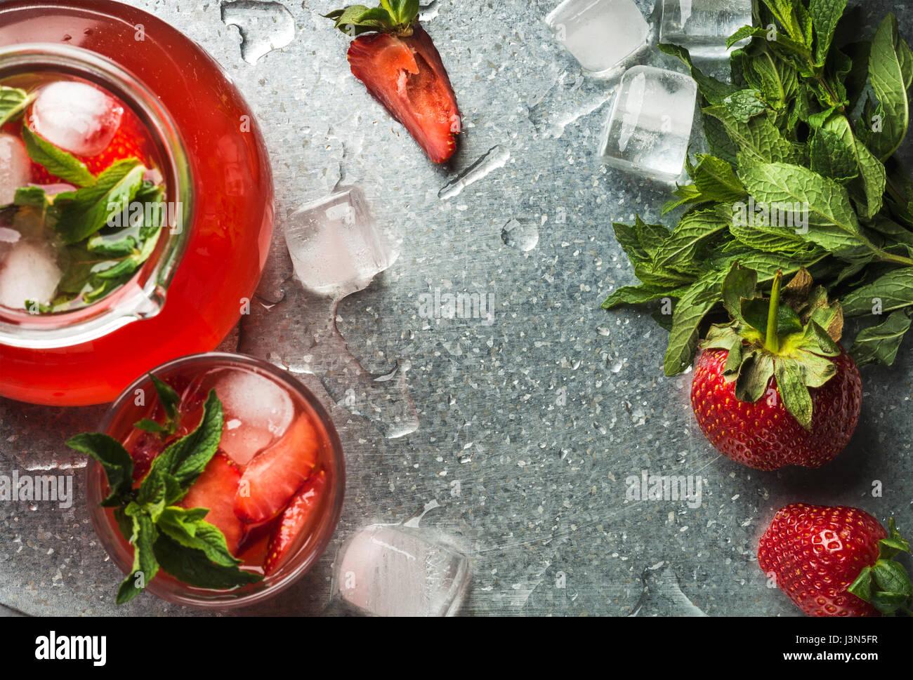 Fresa caseros limonada con menta, hielo y bayas frescas sobre la bandeja de metal de fondo, vista superior, espacio Imagen De Stock