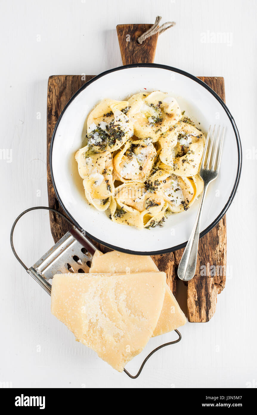 Tortellini italianos Burro e salvia con carne ahumada, mantequilla y salvia en placa de madera rústica sobre Imagen De Stock