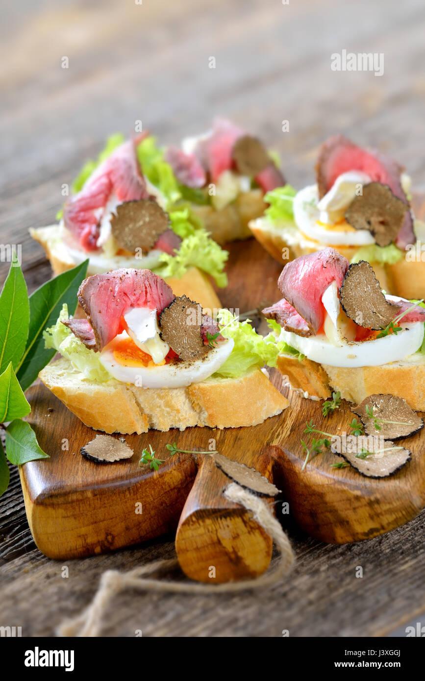 Canapés con roast beef, otoño negras trufas, queso brie francés sobre una rebanada de huevo en baguette con una hoja de ensalada Foto de stock