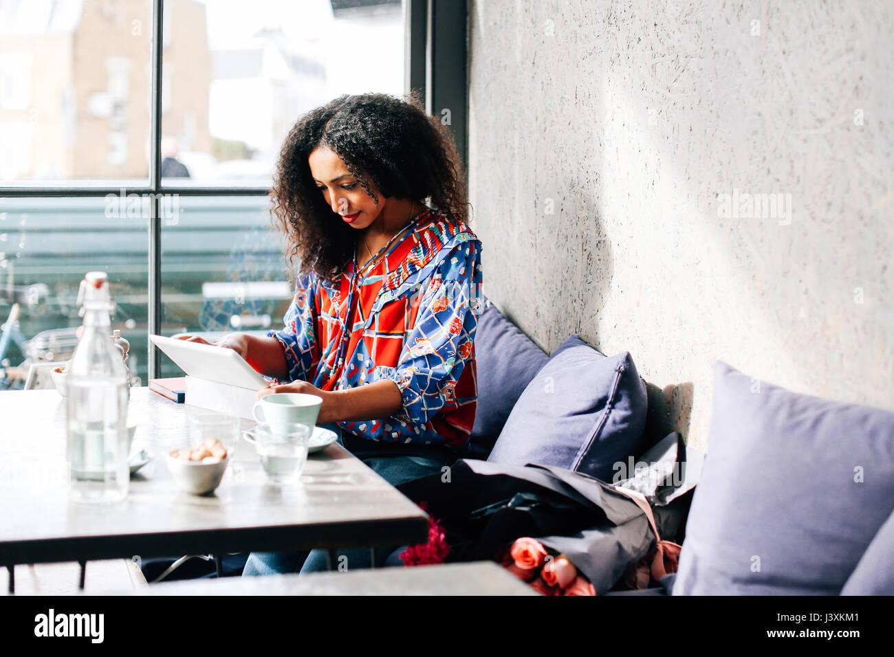 Mujer adulta media utilizando digital comprimido en cafe Imagen De Stock
