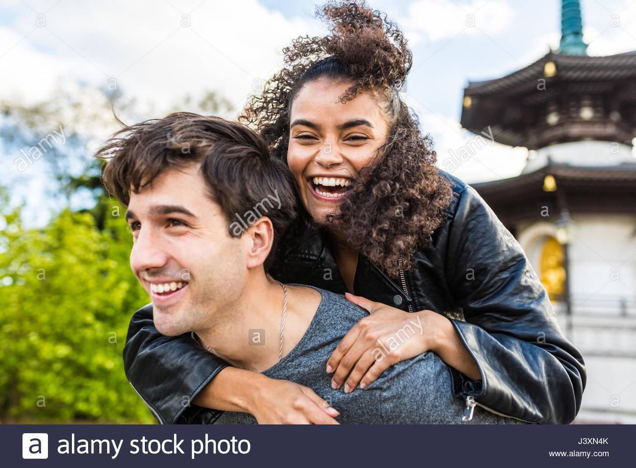 Mujer joven obteniendo piggyback de novio en Battersea Park Imagen De Stock