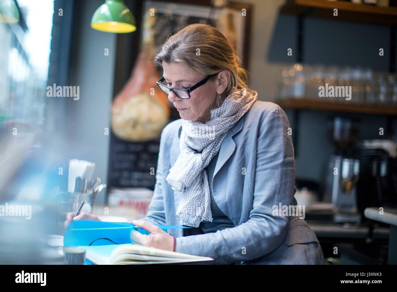 Empresaria madura haciendo papeleo en restaurante. Imagen De Stock