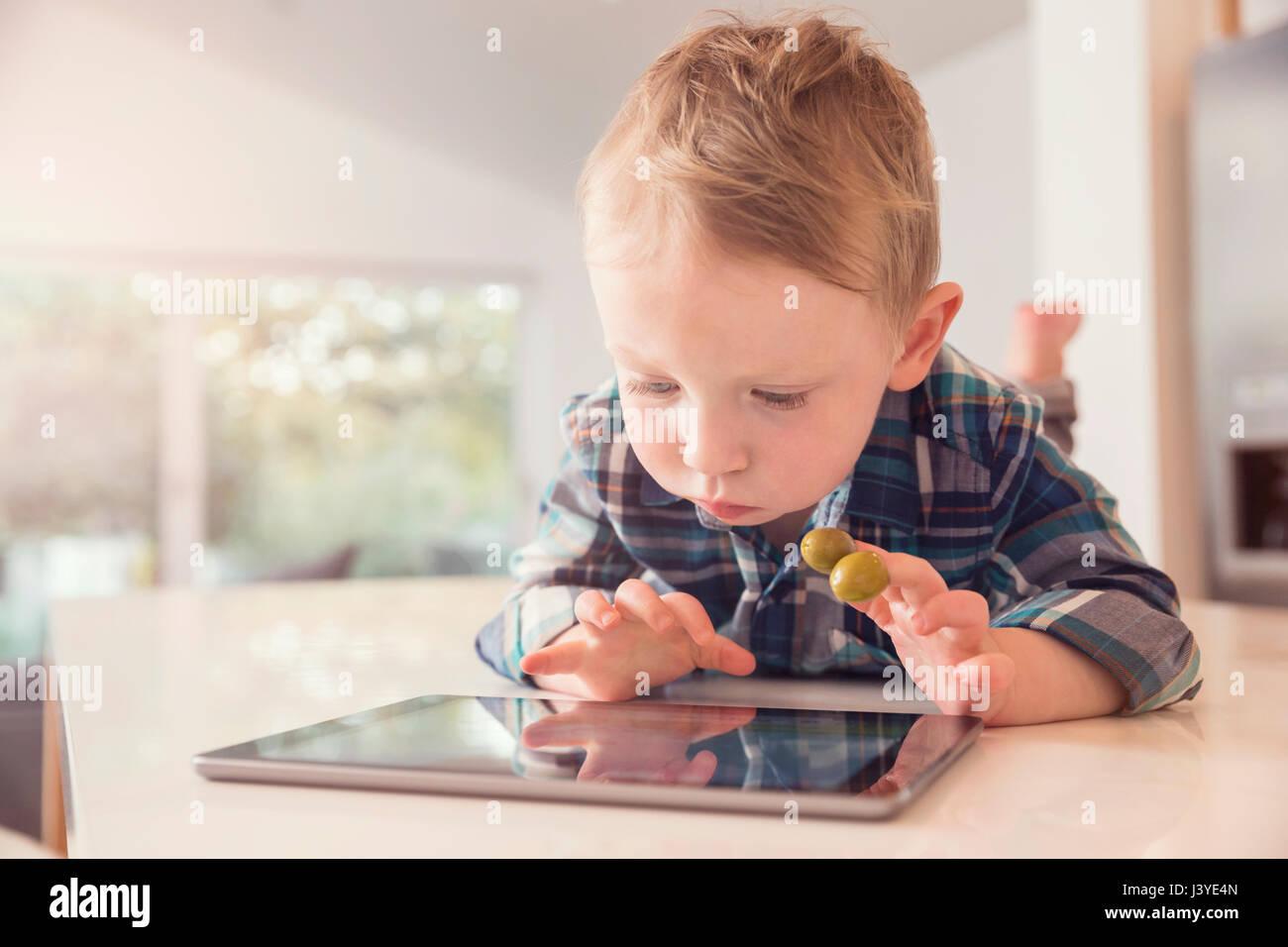Niño Chico mirando en tablet comiendo aceitunas en cocina en casa Foto de stock