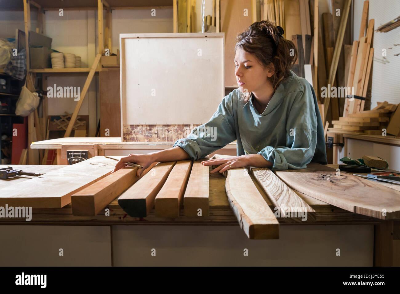 Mujer joven eligiendo la madera de una selección en un taller Foto de stock