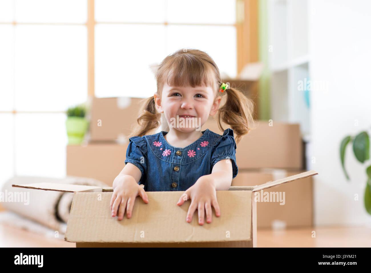 Acaba de mudarse a una nueva casa. Kid se encuentra dentro de la caja. Foto de stock