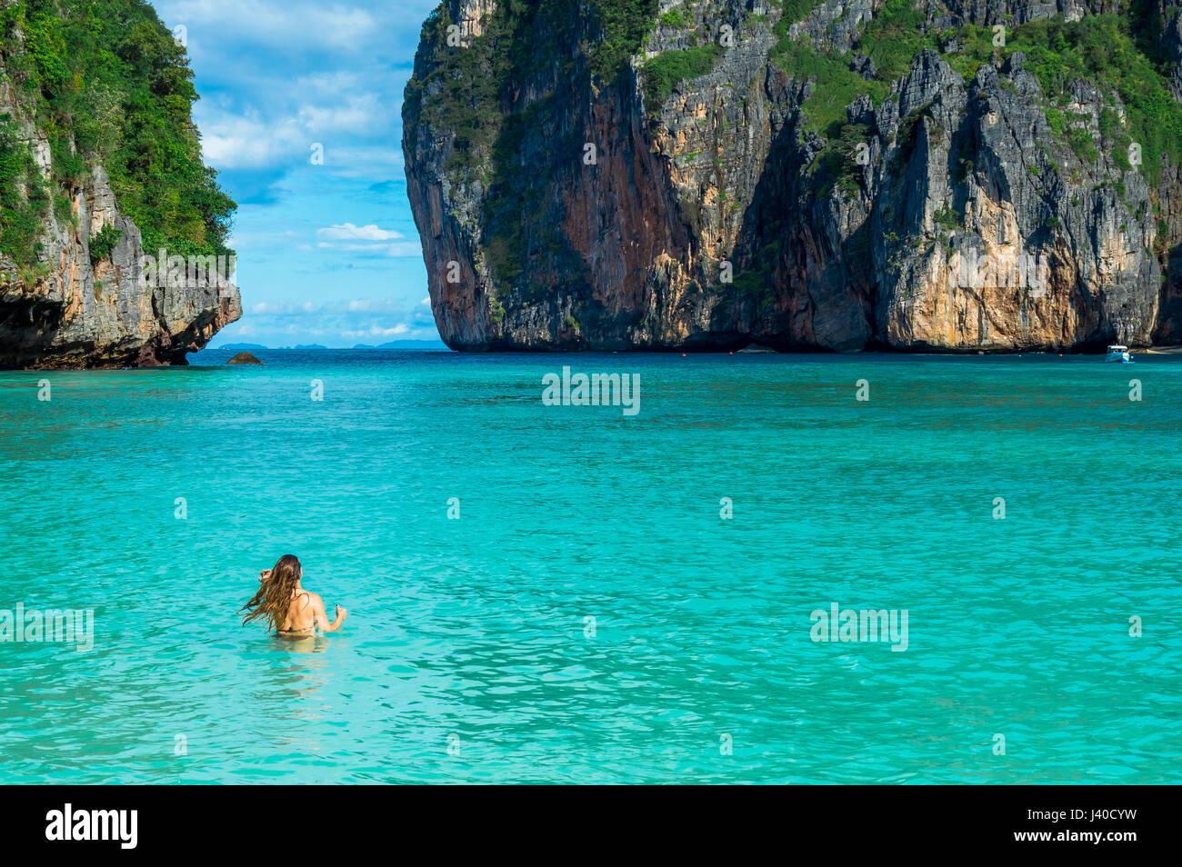 Vista panorámica de la mujer por mar contra las formaciones rocosas Imagen De Stock