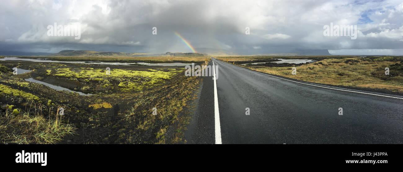 Carretera vacía en Islandia. Vista con montañas rocosas en el fondo. Hermosa cordillera int Islandia es difícil Foto de stock