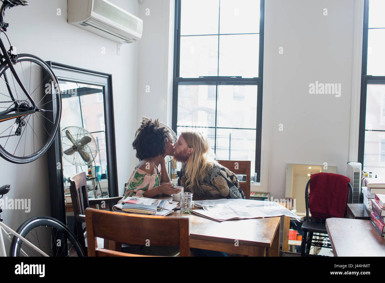 Una joven pareja besándose en una mesa de comedor Imagen De Stock