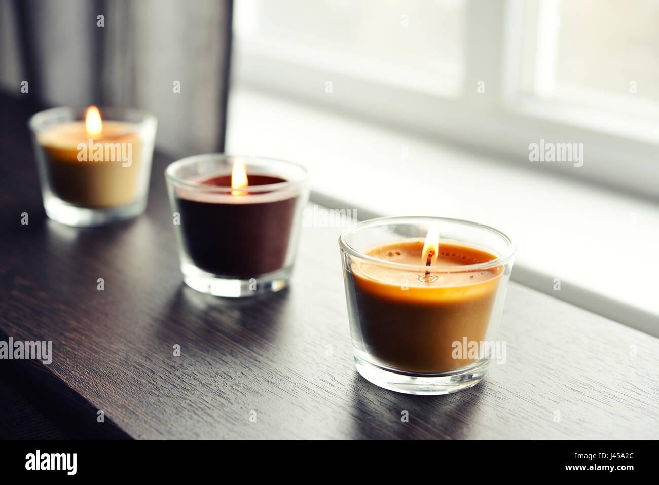 Acogedoras velas en una mesa de madera en interiores closeup Foto de stock