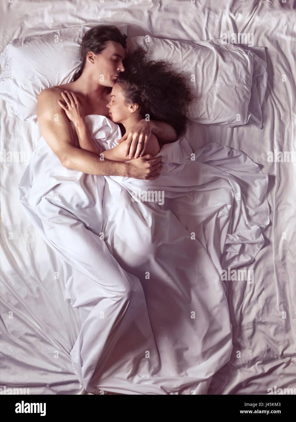 Pareja durmiendo juntos en un enbrace en cama en un dormitorio iluminado por la luz del sol de la mañana brillante Foto de stock