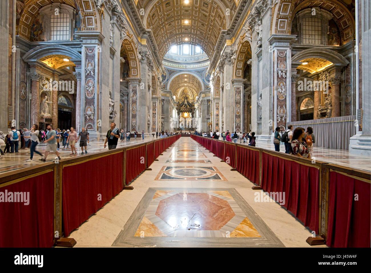 Un amplio ángulo de vista interior dentro de la Basílica de San Pedro con los turistas que caminan. Imagen De Stock