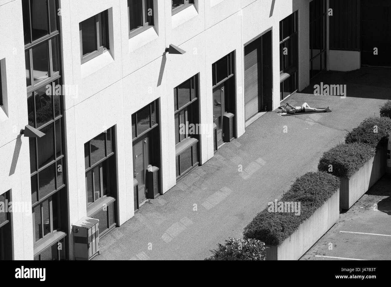 Una vista general de un sol de una mujer fuera de un bloque de oficinas y junto a un aparcamiento de coches en la Foto de stock