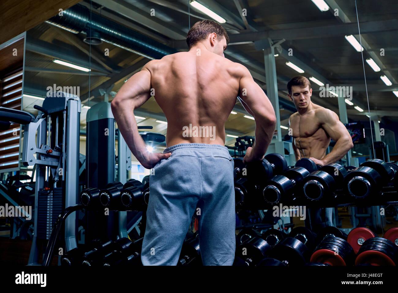 Vista trasera de un deportivo de hombre con los músculos en el gimnasio. Imagen De Stock
