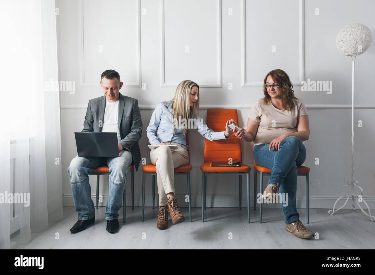 Un grupo de jóvenes creativos sentadas en sillas en la sala de espera. Imagen De Stock
