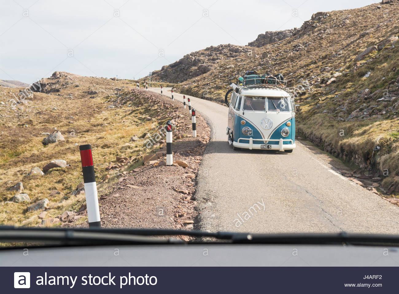 Costa norte 500, Escocia - classic VW camper van utilizando un lugar de paso en el Bealach na Ba road, visto a través Imagen De Stock