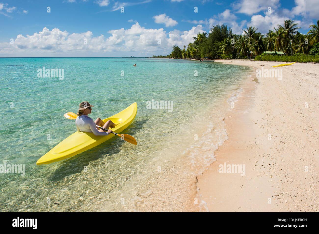 Mujer kayak en las aguas turquesas de Tikehau, Tuamotus, Polinesia Francesa, el Pacífico Imagen De Stock