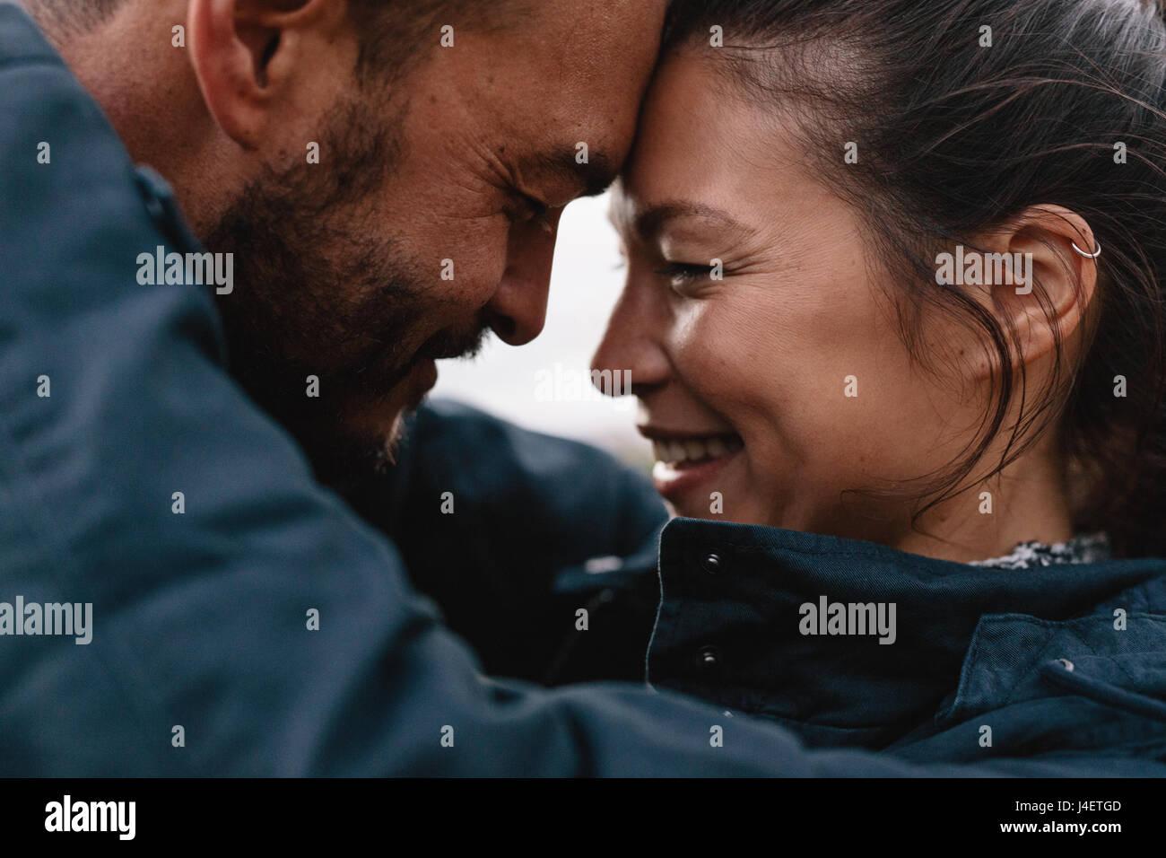 Cierre lateral de retrato de joven pareja de raza mixta en el amor. Pareja abrazándose entre sí y sonriente. Imagen De Stock