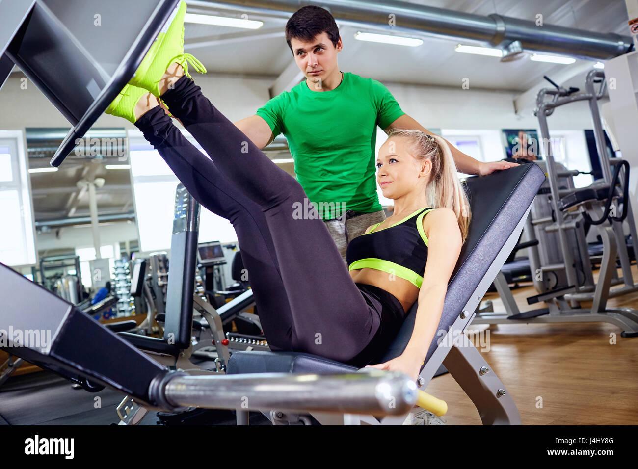 Una chica está haciendo ejercicios en el simulador de pie con personal t Imagen De Stock