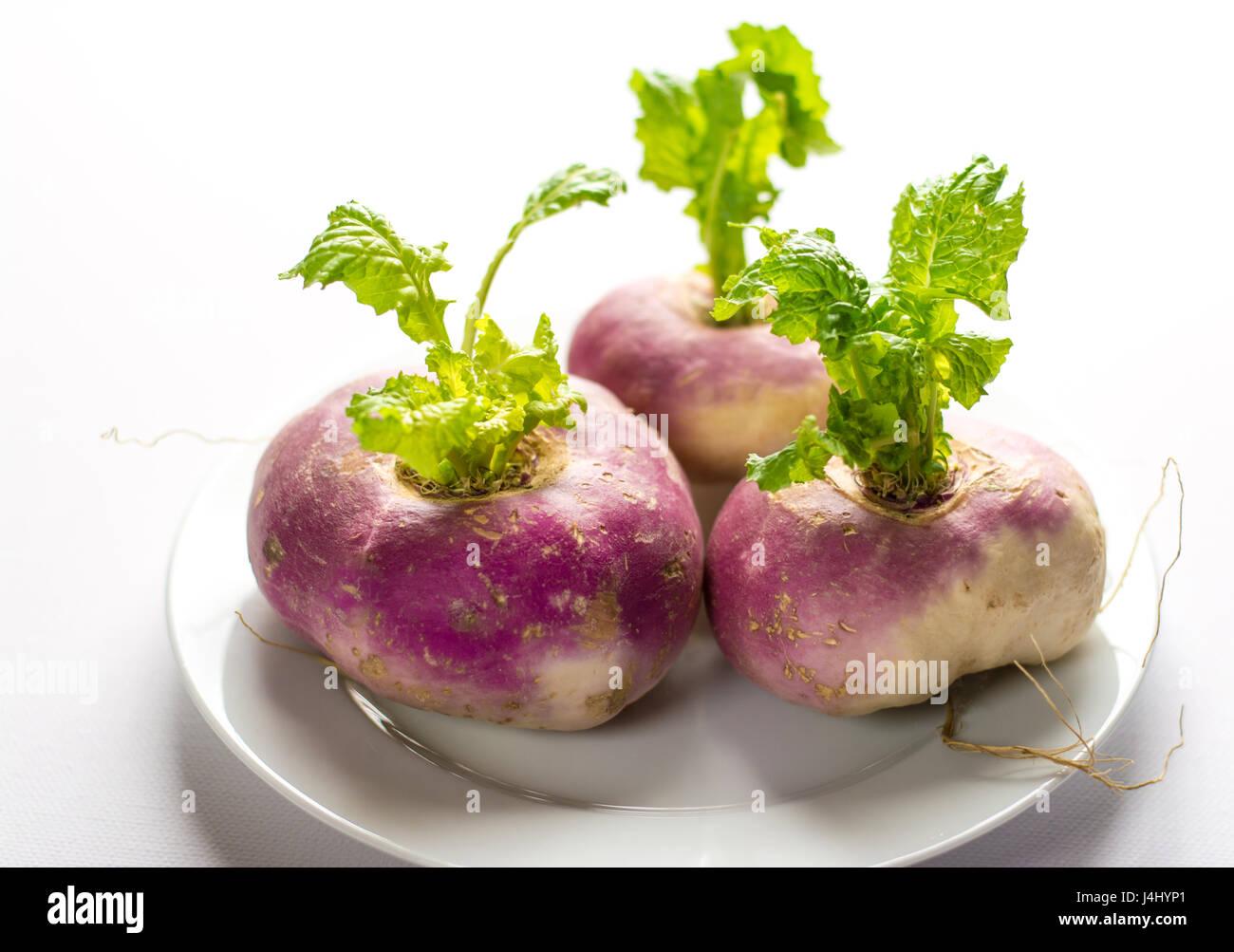 Primer plano de tres orgánicos nabos púrpura con hojas en una placa blanca y antecedentes Imagen De Stock
