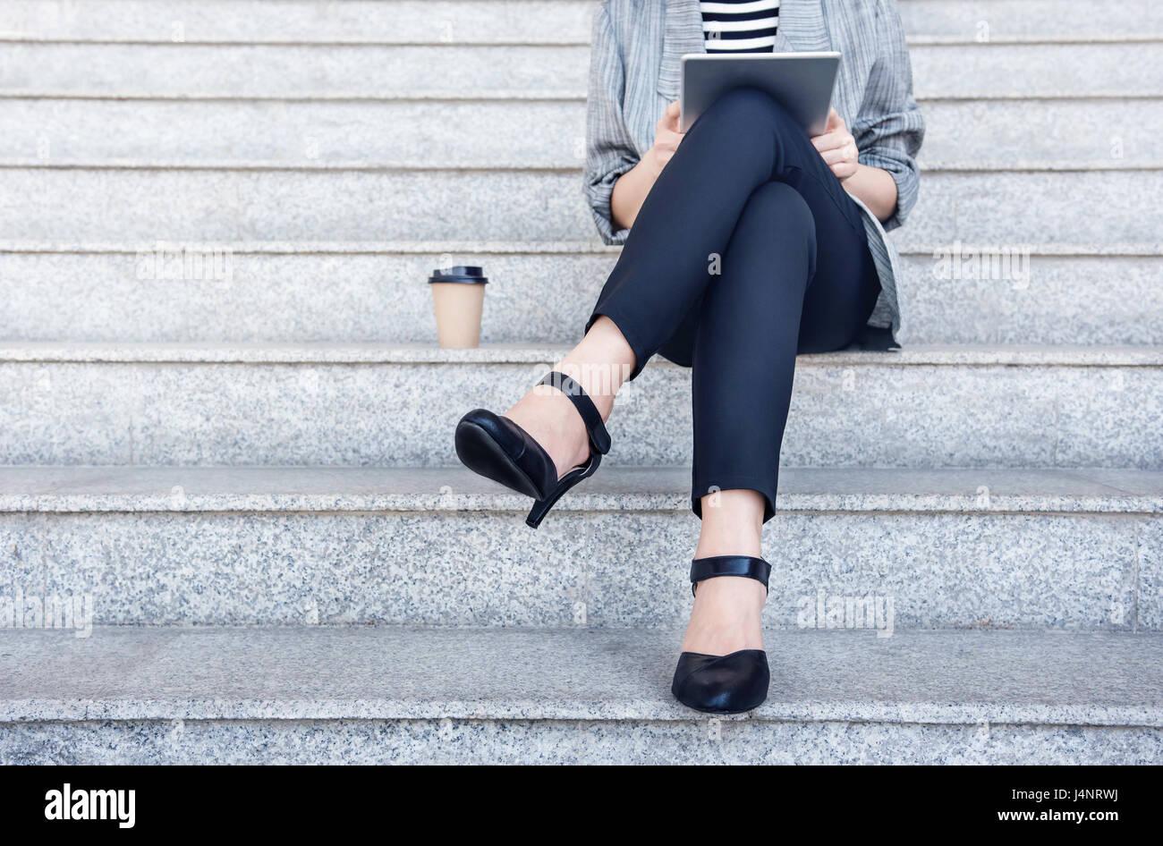 Negocio trabajar mujer sentada y utilizando tablet digital en escalera exterior, vista frontal, Sociales comunicar Imagen De Stock