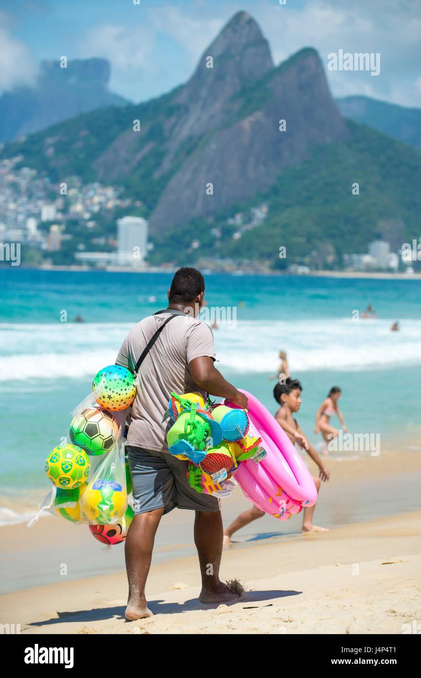 RIO DE JANEIRO - Febrero 10, 2017: un proveedor de playa de colorida balones de playa y juguetes lleva su pantalla Imagen De Stock