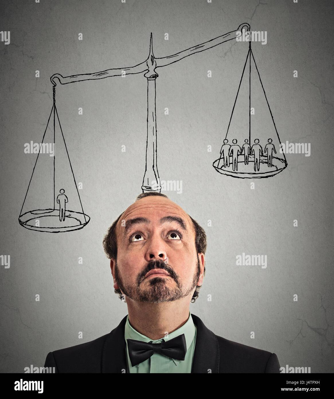 Empresario con escala de ponderación sobre la cabeza de un hombre más del grupo fuera de gente de negocios Imagen De Stock