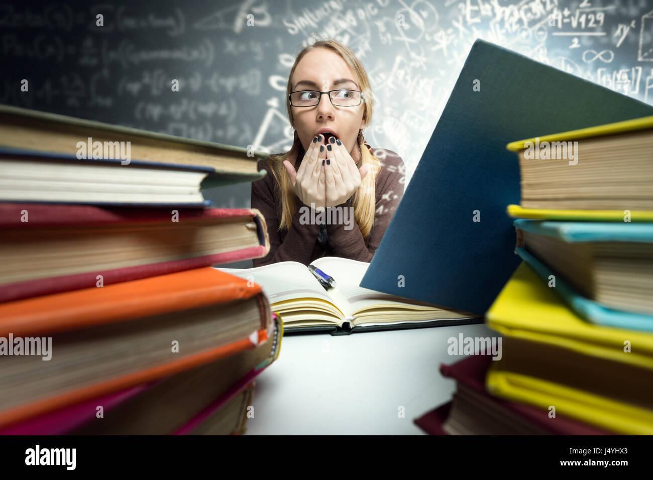 Conmocionado schoolgirl buscando en libro abierto con fórmulas mágicas Foto de stock