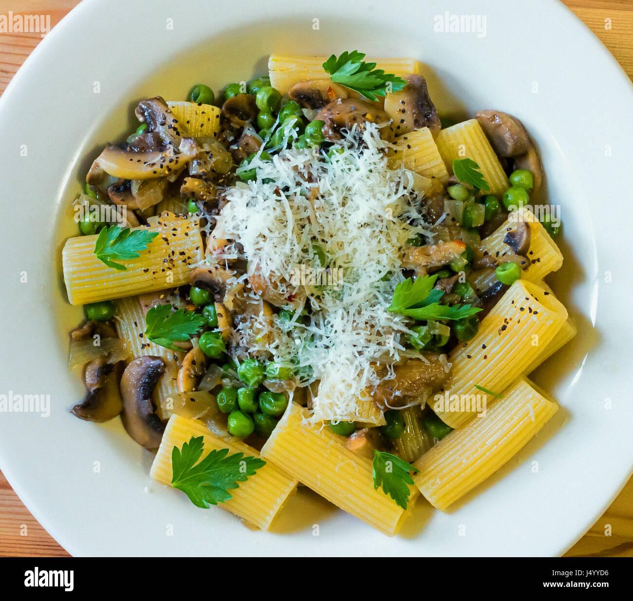 Rigatoni Pasta con champiñones, guisantes, mantequilla y queso Reggiano Parmigano Imagen De Stock