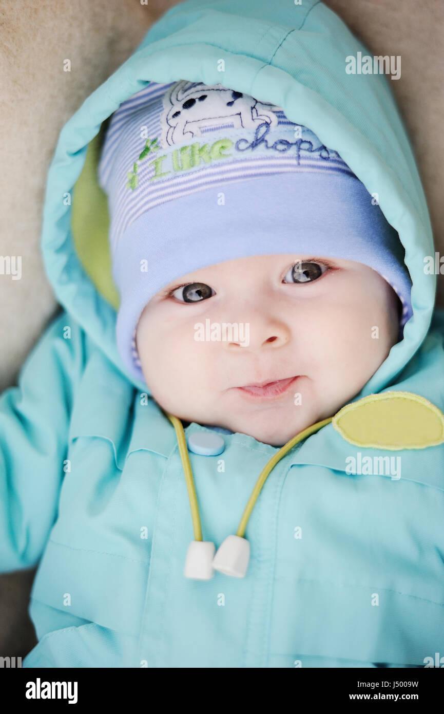 Bebé en chaqueta azul sonriendo ante la cámara Imagen De Stock