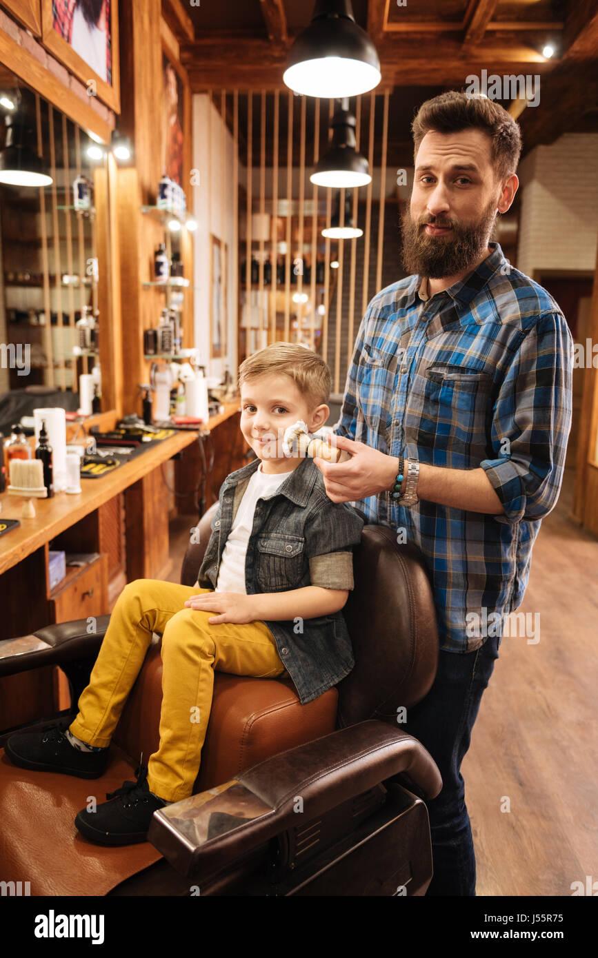 Chico lindo alegre siendo afeitado Foto de stock