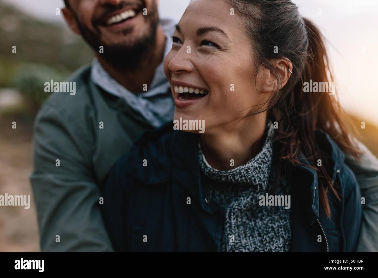 Sonriente mujer asiática es abrazado por su novio desde atrás. Par disfrutar de vacaciones. Imagen De Stock