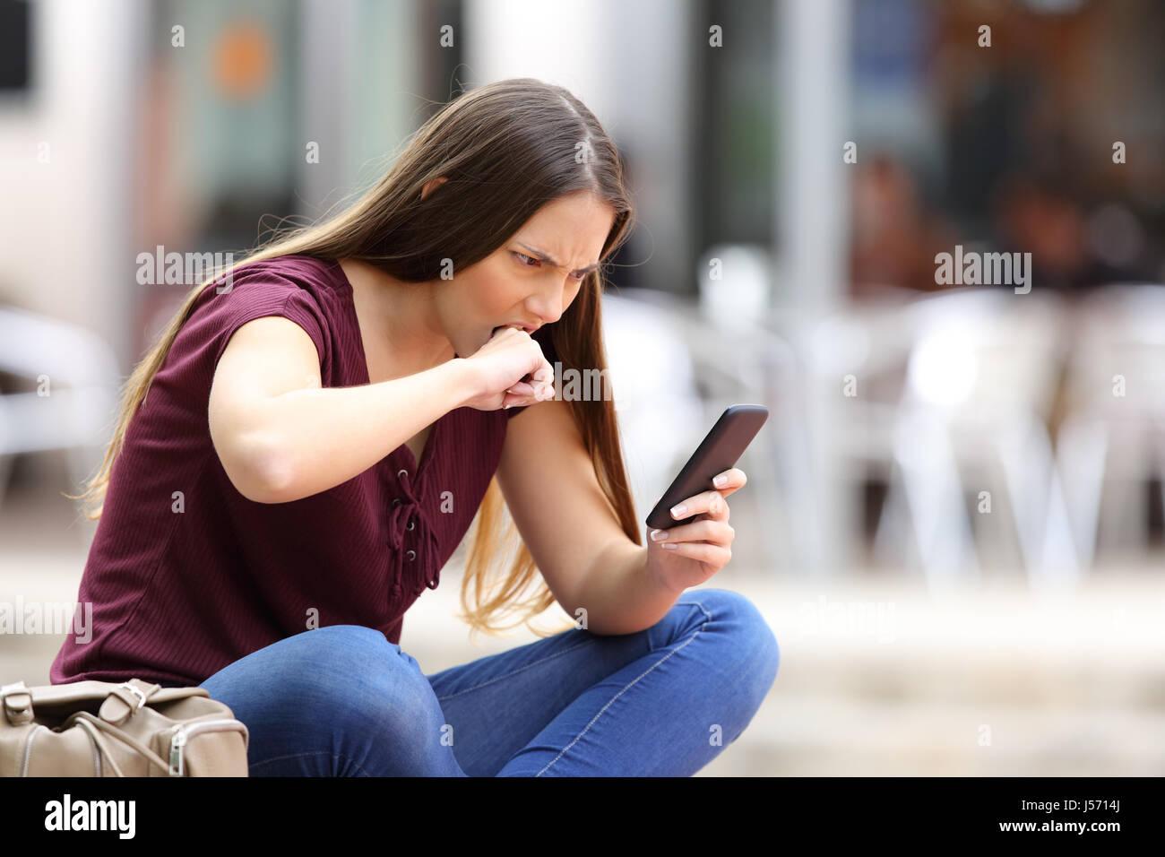 Enojado mujer recibiendo mal contenidos en línea en un teléfono móvil sentado en un banco en la calle Imagen De Stock