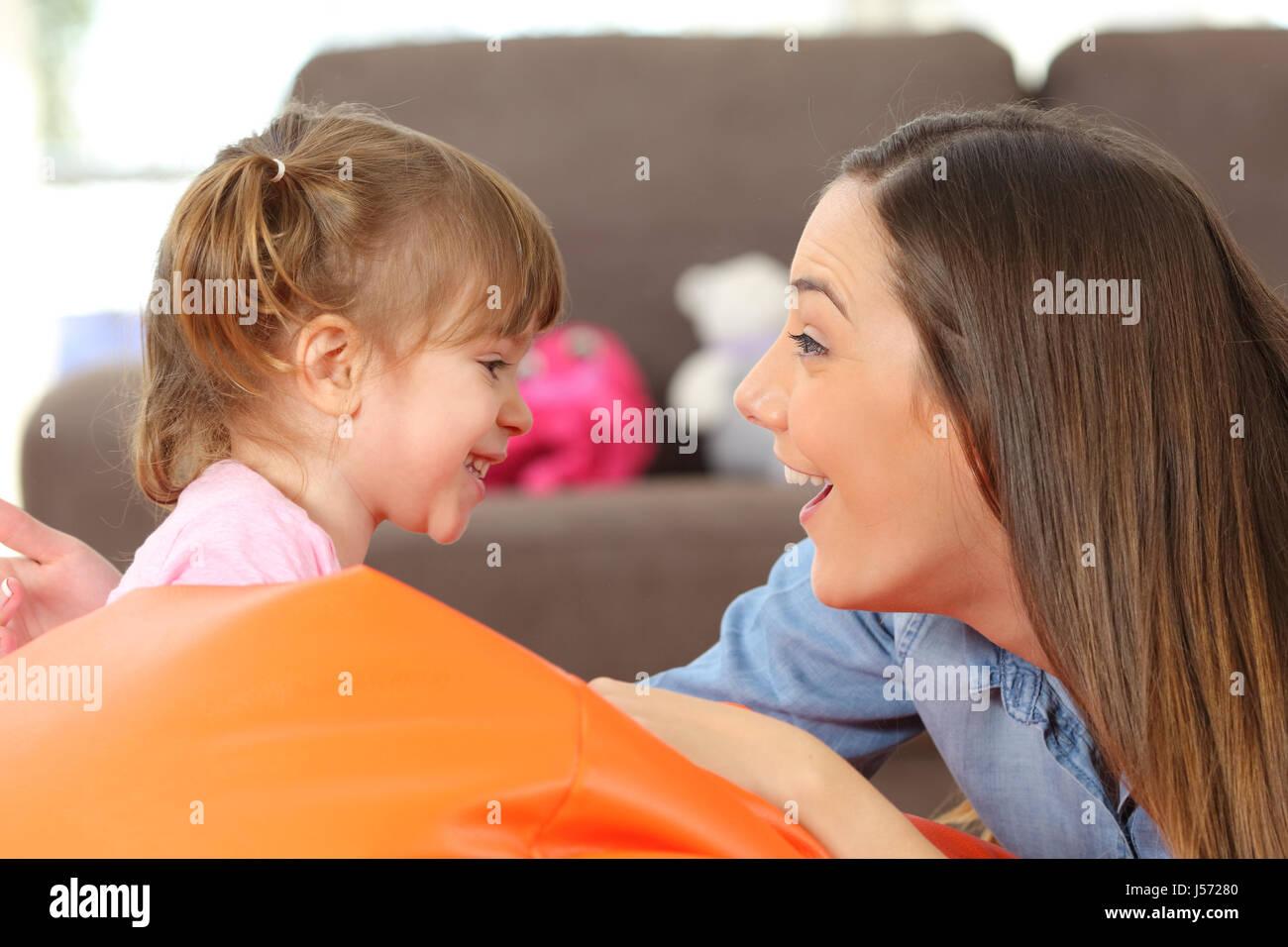 Vista lateral retrato de una feliz madre e hija de 2 años mirando y bromas en el salón en casa Imagen De Stock