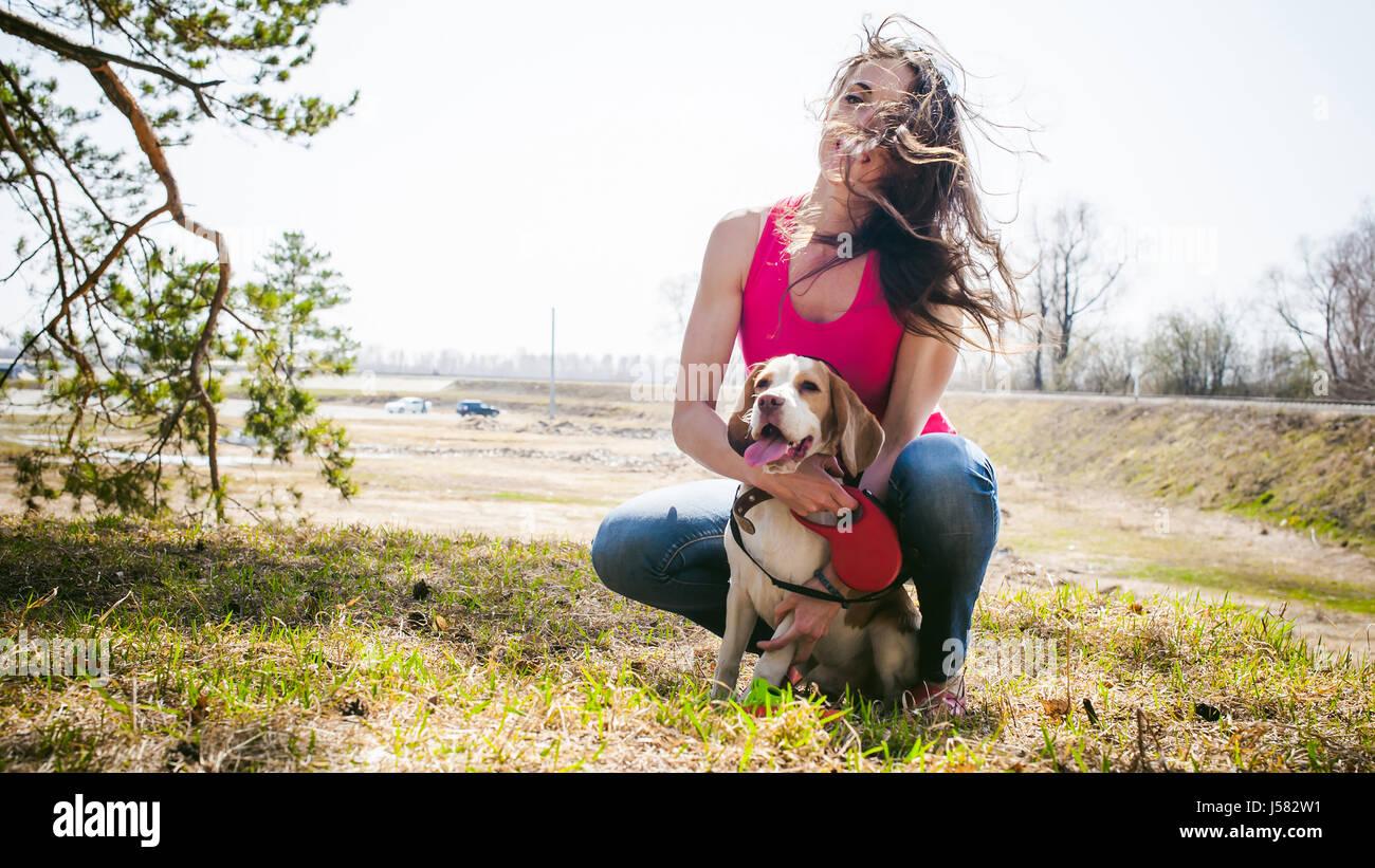 Jóvenes de razas de perro Beagle a caminar en el parque al aire libre. La muchacha camina cuidadosamente el Imagen De Stock