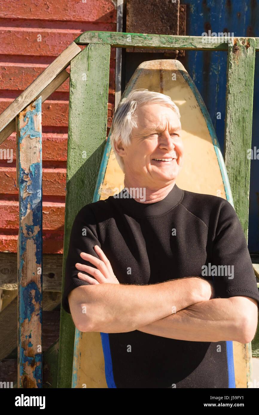 Hombre con tabla de surf contra daño permanente en la playa en día soleado Imagen De Stock