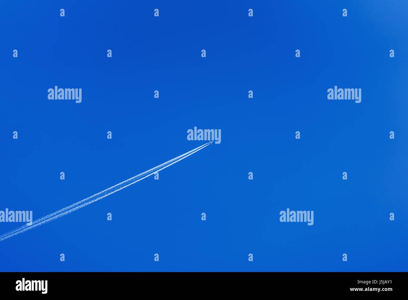 Avión volando dejando huella en diagonal un cielo azul sin nubes. Espacio para copiar el texto, moderno, patrón Imagen De Stock