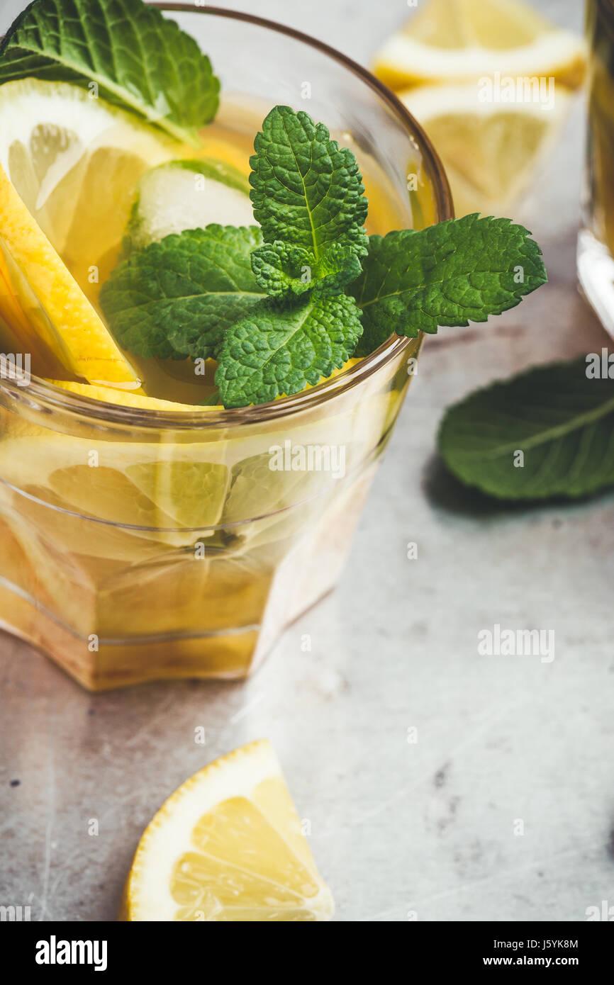 Limón helado casero té dulce con menta en la tabla de color gris claro, un delicioso refresco copa de Imagen De Stock