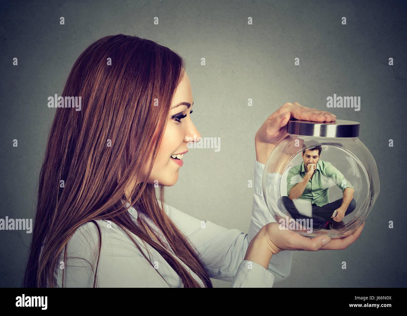 Mujer sosteniendo un tarro de vidrio con hombre encarcelado en ella Imagen De Stock