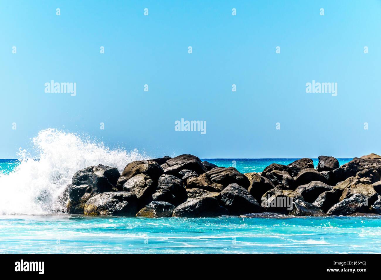 Olas rompiendo sobre las barreras que crean las lagunas de Ko Olina en la costa oeste de la isla hawaiana de Oahu. Las lagunas ideales para nadar Foto de stock