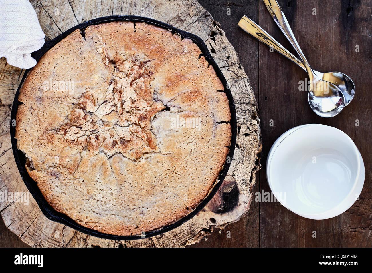 Imagen de arriba de un arándano y peach cobbler horneado en una sartén de hierro fundido sobre una mesa de madera Foto de stock