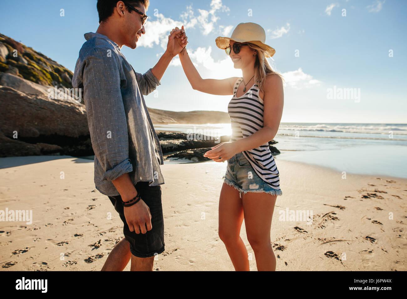 Foto de joven y mujer bailando en la playa en un día de verano. Romántica pareja joven bailando en la Imagen De Stock