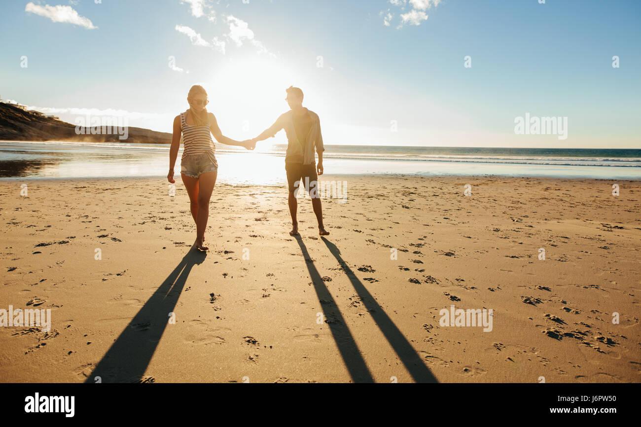 Disparó al aire libre de la romántica pareja joven caminando por la orilla del mar cogidos de la mano. Imagen De Stock