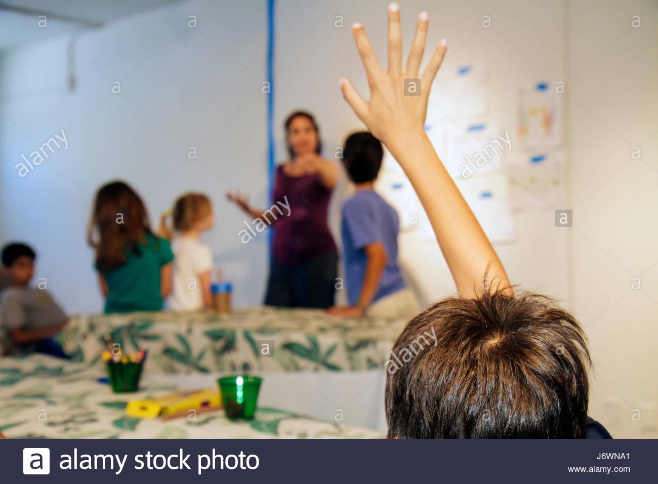 Miami Beach Florida ArtCenter South Florida Art Camp class boy planteadas levantando la mano maestra Imagen De Stock