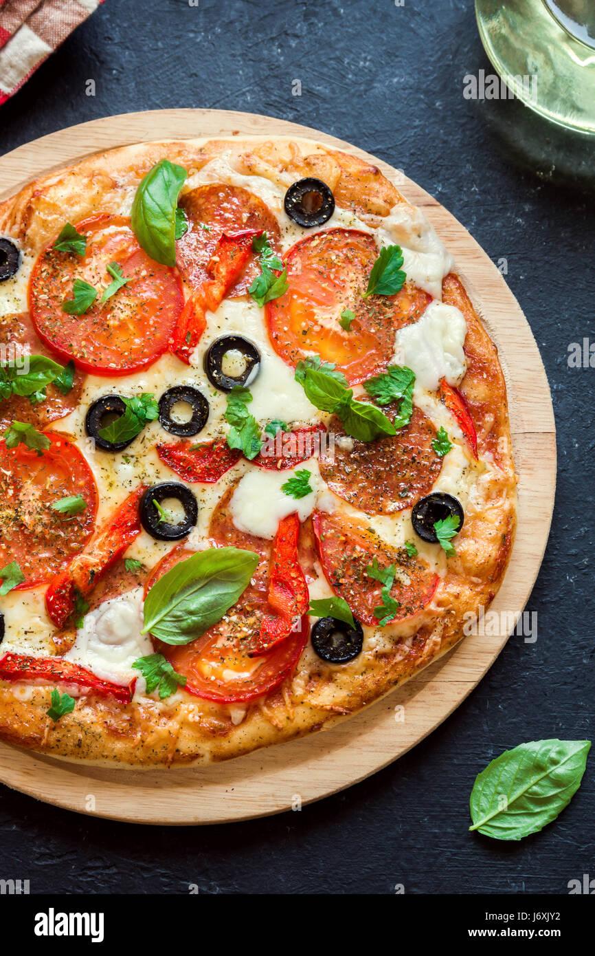 Pizza con tomates, salame, aceitunas negras y queso mozzarella, vista desde arriba. Pizza casera dulce. Imagen De Stock