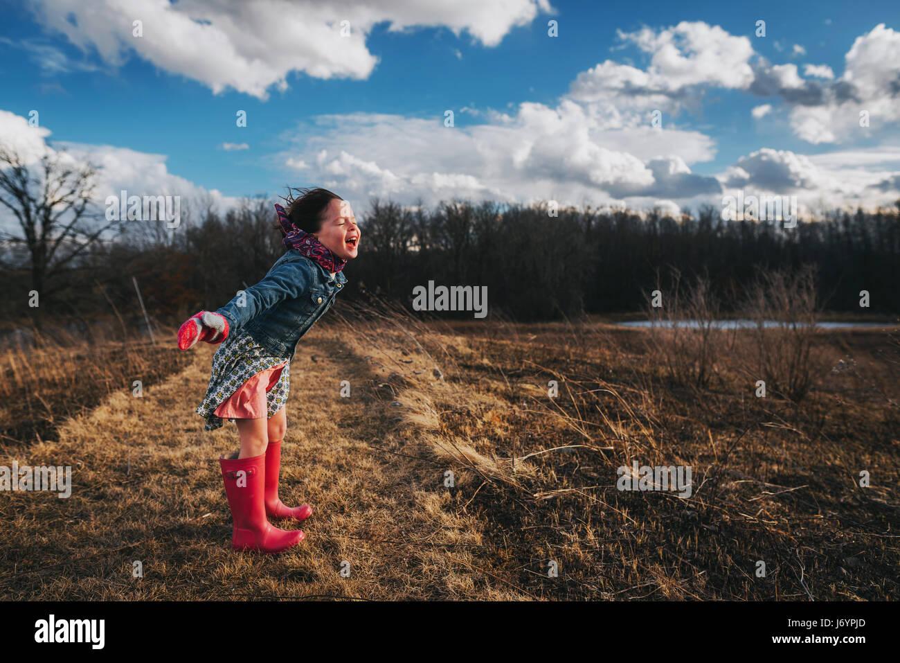 Niña con los brazos extendidos gritando en el viento Foto de stock