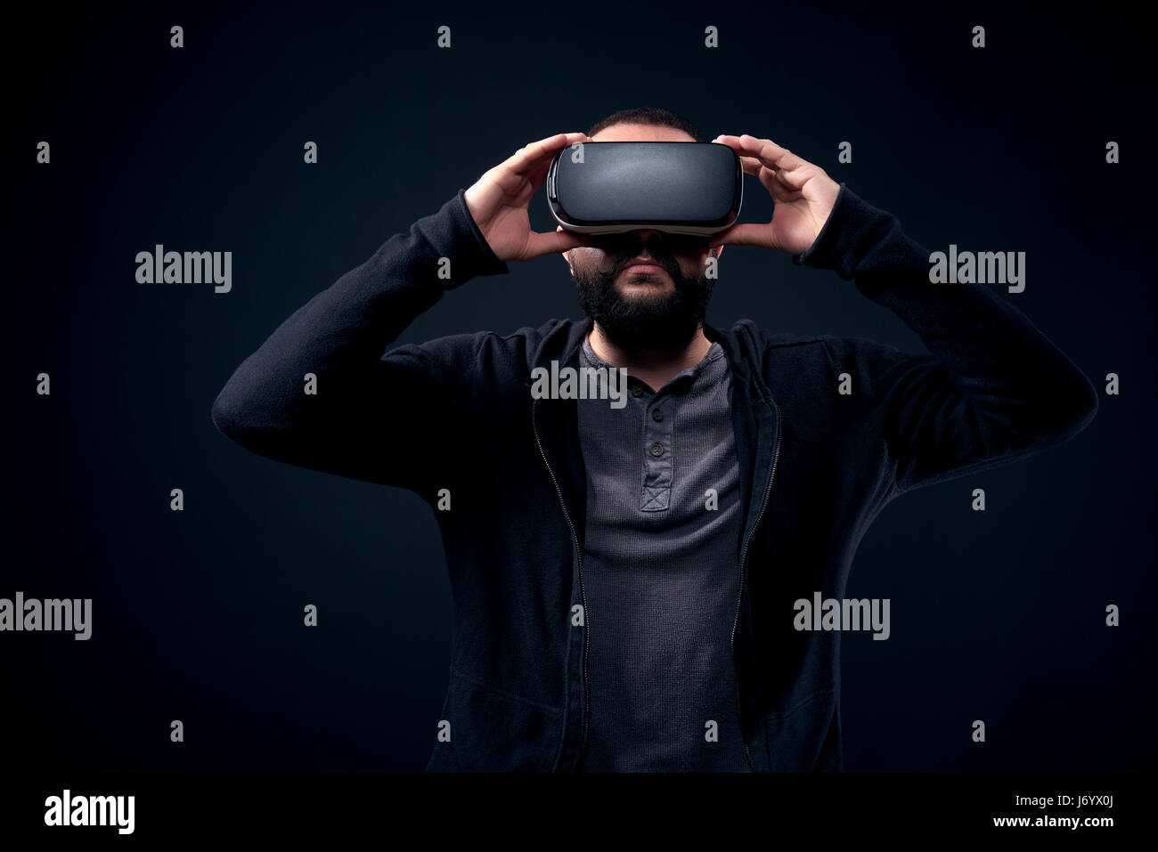 Young hipster hombre barbado portando gafas de realidad virtual. fondo negro studio concepto vr Imagen De Stock