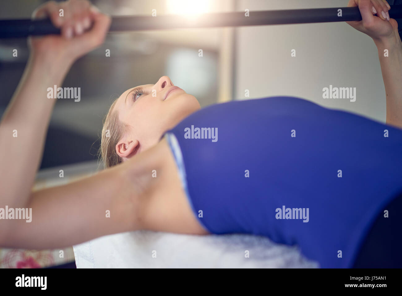 Vista lateral cerca de la joven mujer rubia en la parte superior azul haciendo ejercicio pulsando la banqueta con Imagen De Stock