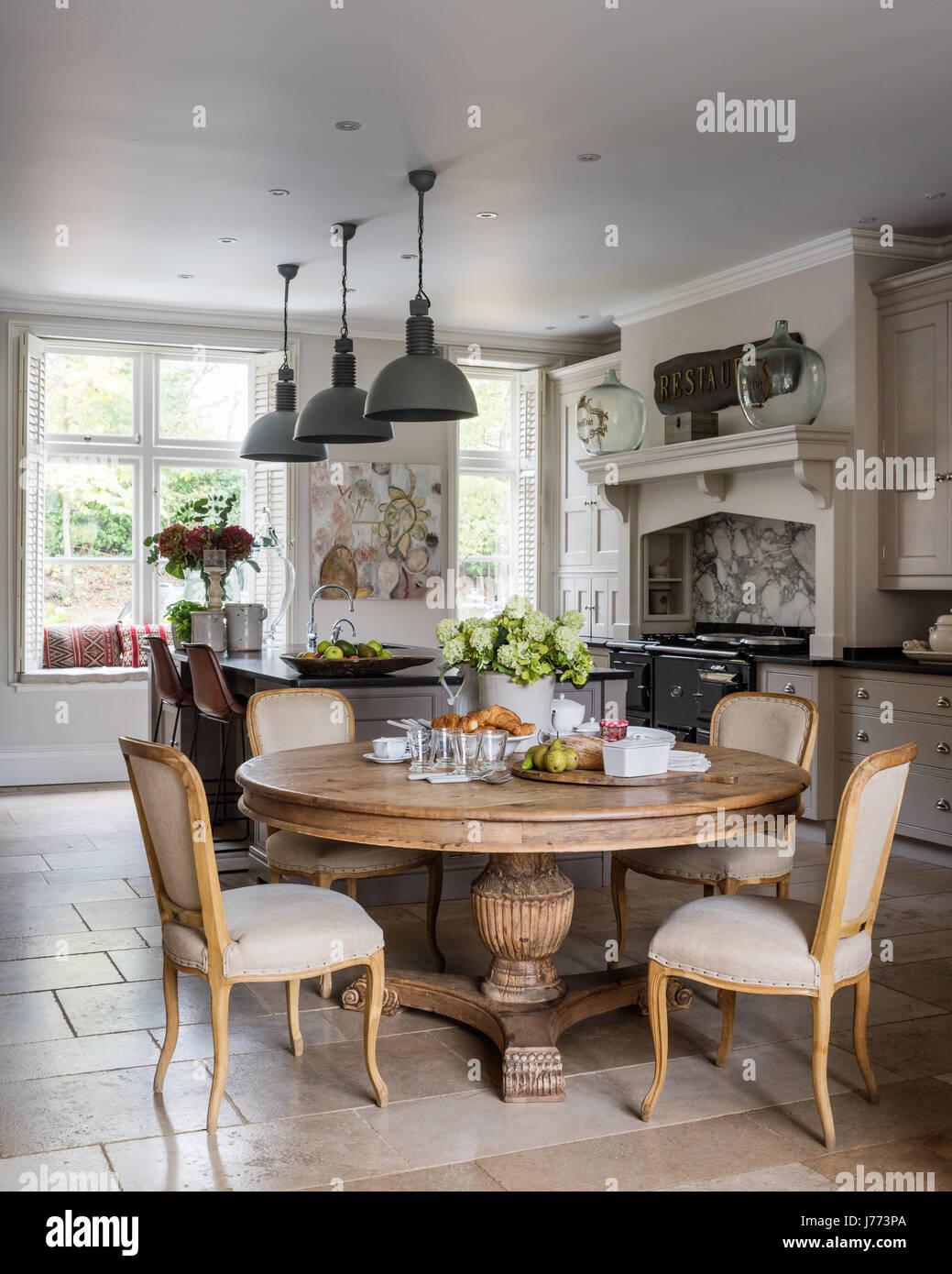 Amplia cocina comedor con baldosas de piedra caliza y muebles de cocina a medida  por Thomas Ford   Sons. Mesa y sillas circular todos por Bardoe   Appel. a5c8514434f1