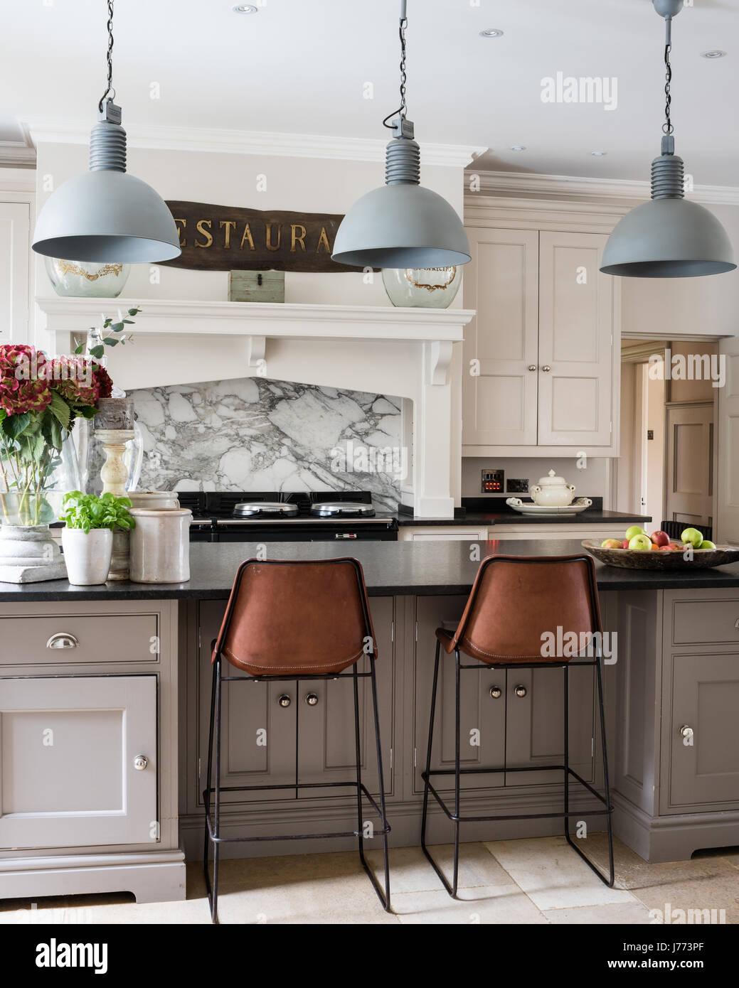 Las lámparas colgantes por Bardoe & Appela bove cocina barra de desayuno. El Sol y Luna taburetes están Imagen De Stock